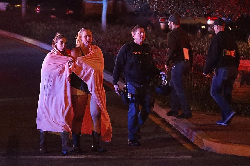 Two women leaving the area near the Borderline Bar and Grill in Thousand Oaks, California, after a gunman went on a shooting spree on Wednesday. The Ventura County Sheriff's office said the bar had been hosting an event for college students, with pos