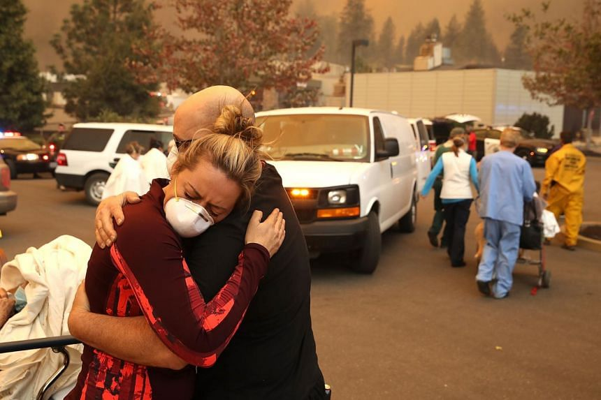 A hospital worker embraces her co-worker as they evacuate patients from the Feather River Hospital during the Camp Fire in Paradise, California, on Nov 8, 2018.