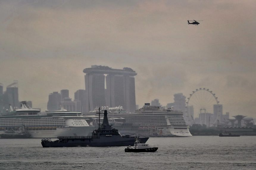 A showcase of a joint patrol by the RSS Independence (left) from the Singapore Navy, the AH-64D Apache helicopter (right) from the Republic of Singapore Air Force, and Porcupine Ray (centre) from the Police Coast Guard in the anchorage off Marina Bar