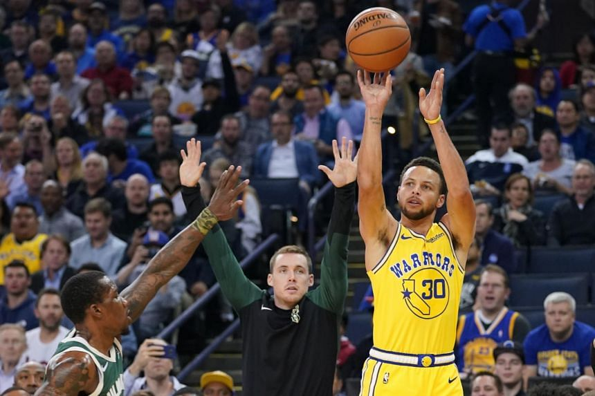 Golden State Warriors guard Stephen Curry (right) shoots the basketball against Milwaukee Bucks guard Eric Bledsoe during the first quarter at Oracle Arena.