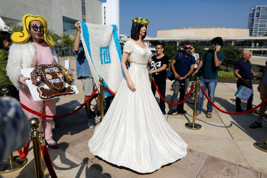 "A man in a costume holds a cake with Hebrew writing ""loyal to the arts"" as he stands next to an installation, including a statue resembling Israeli Minister of Sports and Culture, Miri Regev, at the plaza of Israel's national theatre, Habima, in Tel"