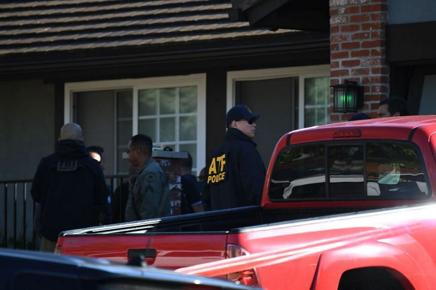 Long's home is cordoned with red crime tape as FBI and ATF officers conduct a search.