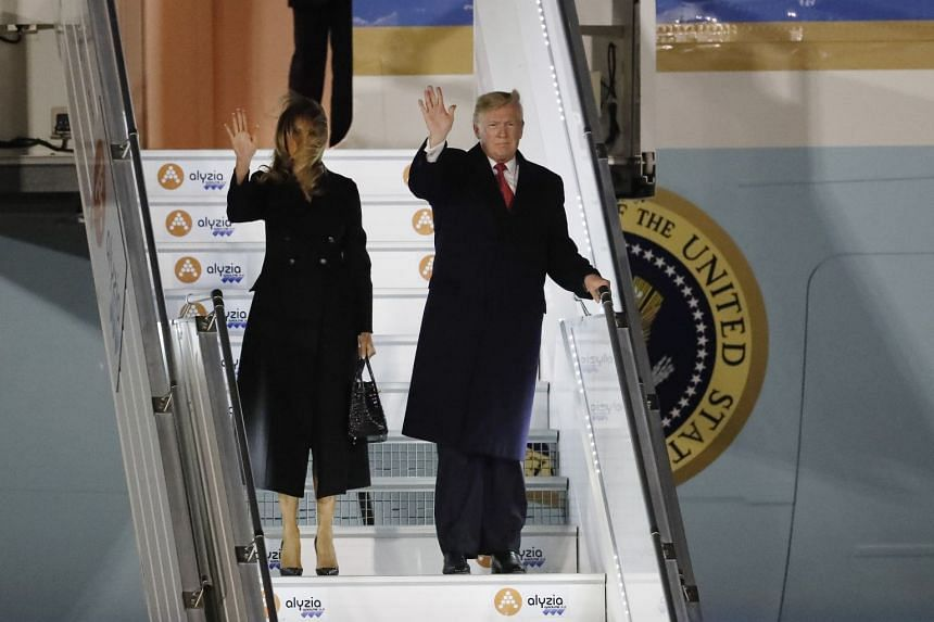 Donald and Melania Trump wave as they disembark from Air Force One upon their arrival in France.