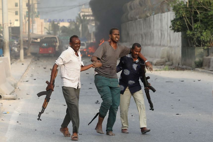 Somali security officers evacuate an unidentified injured man from the scene of an explosion.