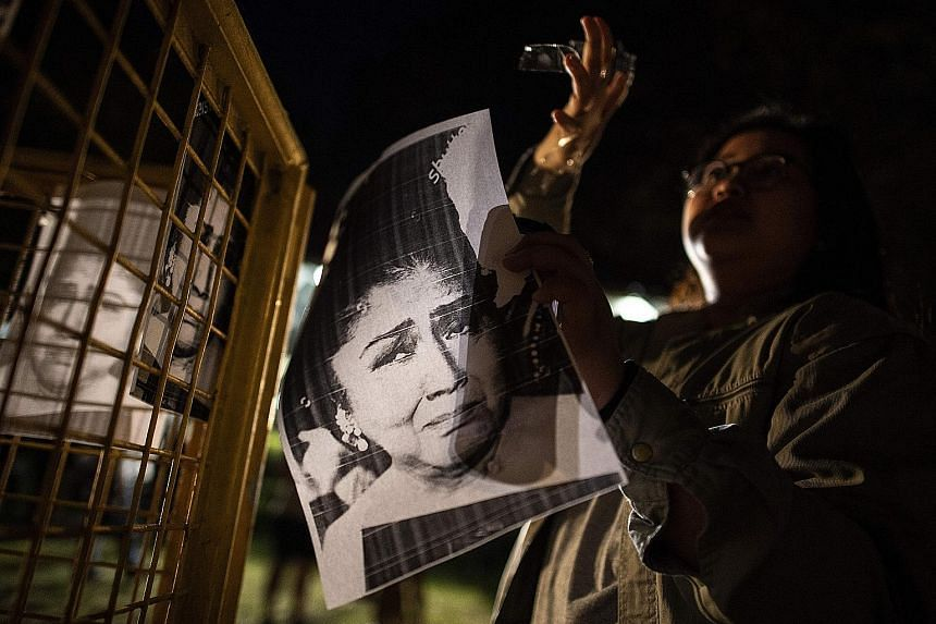 A student with a picture of Imelda Marcos at a rally to mark her corruption conviction at the University of the Philippines yesterday.