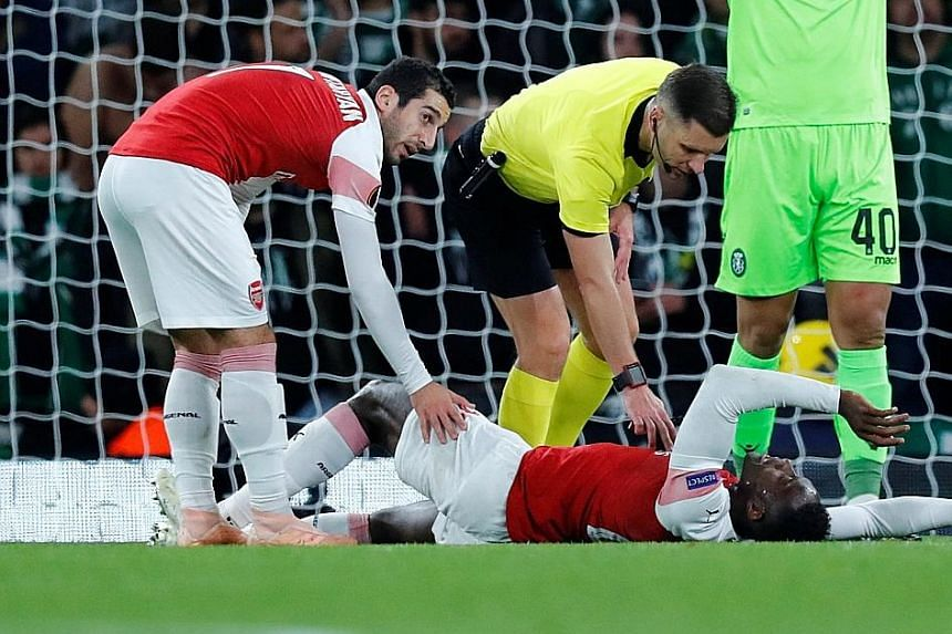 Referee Gediminas Mazeika and Arsenal's Henrikh Mkhitaryan check on Danny Welbeck after the striker suffered a potentially season-ending ankle injury in the Europa League Group E encounter at the Emirates Stadium on Thursday.