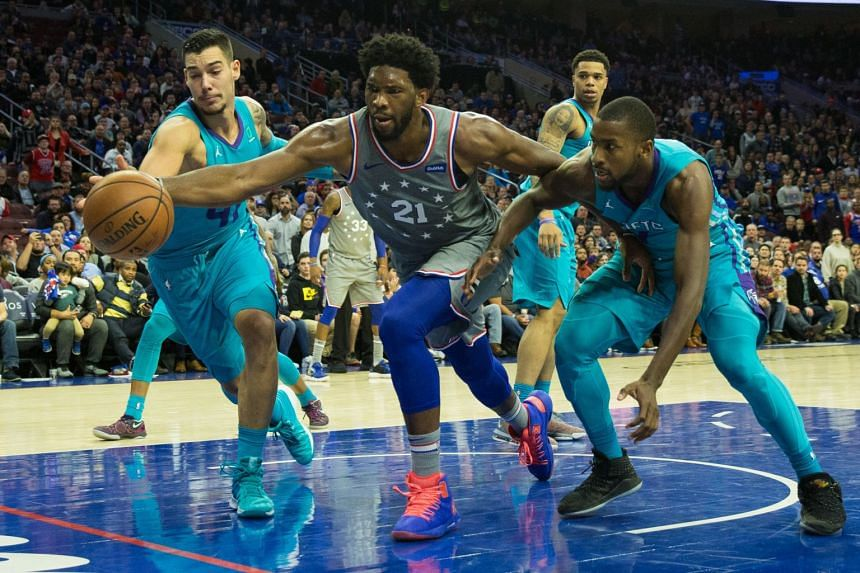 Philadelphia 76ers' Joel Embiid (second from left) lunges past Charlotte Hornets' Willy Hernangomez (left) and forward Michael Kidd-Gilchrist to save the ball from going out of bounds in overtime at Wells Fargo Center.