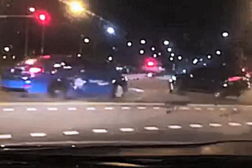 The blue ComfortDelGro taxi skids sideways across the junction from the force of the impact, while broken parts fly out and scatter across the ground from the black car.