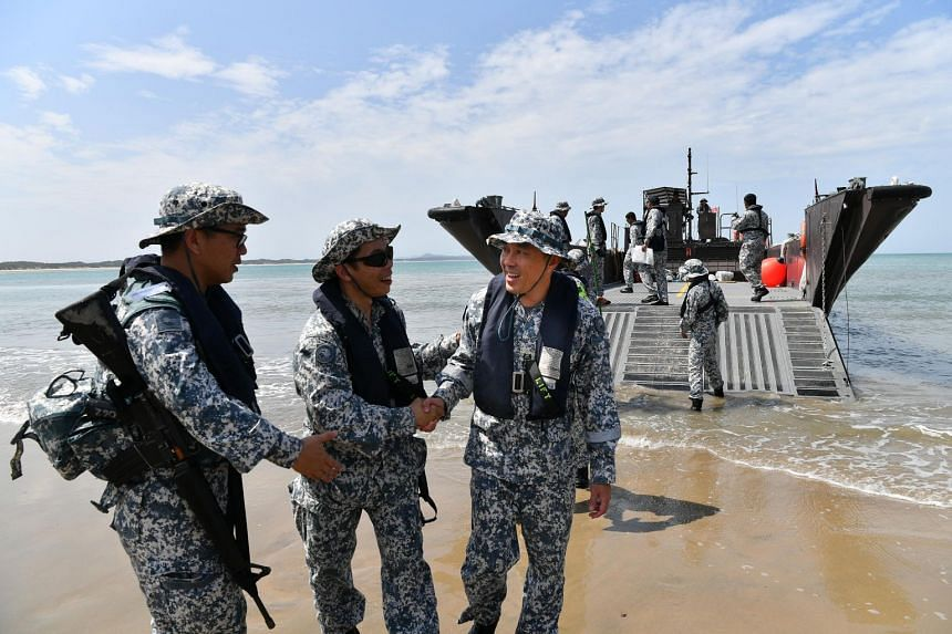 Lieutenant-Colonel Kenny Chen (third from left), head of the RSN's Command Task Group, being greeted after disembarking from a fast craft in the Shoalwater Bay Training Area.