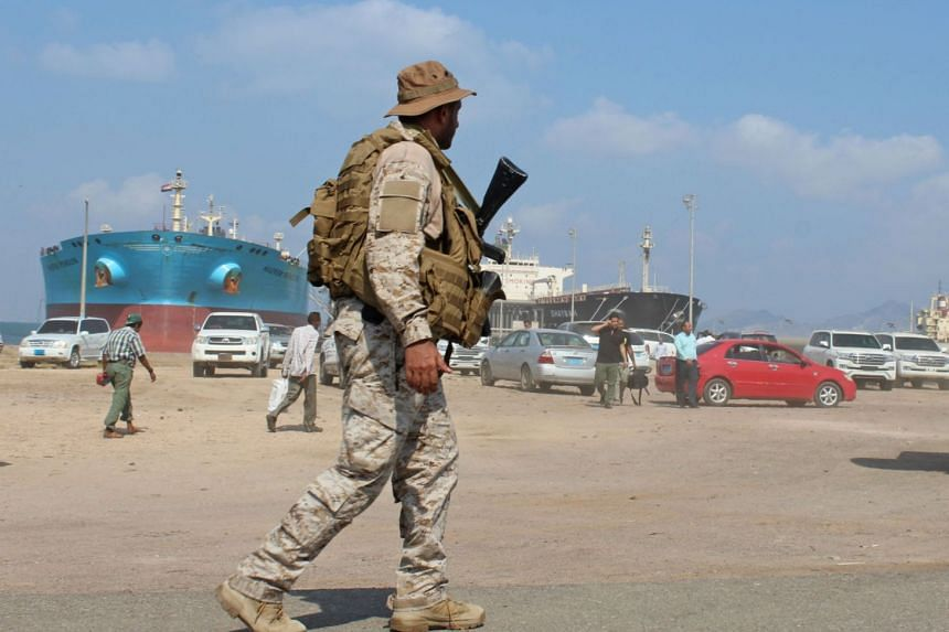 A soldier loyal to Saudi-led coalition forces stands guard near ships docked in the southern Yemeni port of Aden, on Oct 29, 2018.