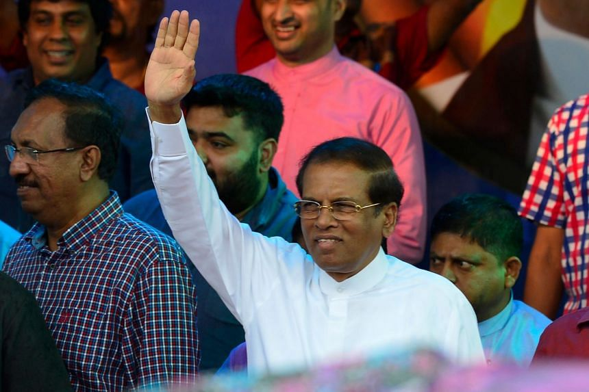 Sri Lanka's President Maithripala Sirisena waves to supporters at a rally in Colombo.