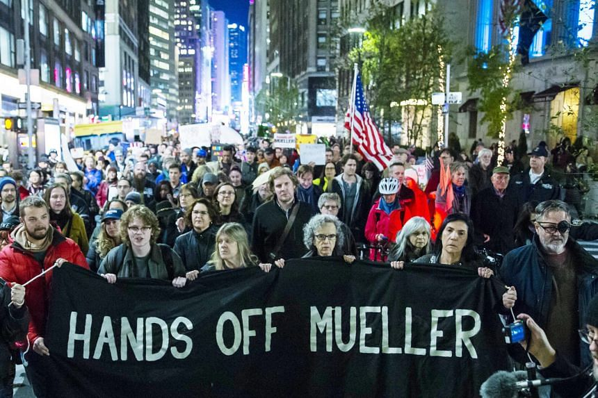 People marching through Times Square in New York City on Thursday night, a day after President Donald Trump forced the resignation of Attorney-General Jeff Sessions. The move has cast doubt on the fate of special counsel Robert Mueller's Russia inves