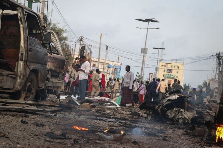 People gather at the scene of twin car bombs that exploded within moments of each other in Mogadishu.