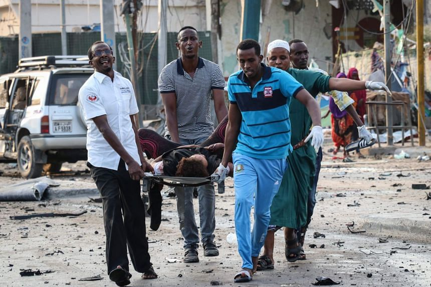 People rescue a wounded person following three suicide car bomb attacks in Mogadishu.