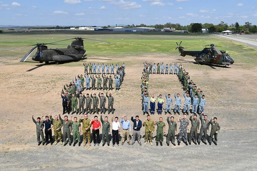 """RSAF officers and their Australian defence partners do a """"20"""" formation with a CH-47D Chinook (left) and AS332 Super Puma (right). Among those in the front row are Senior Minister of State for Defence Heng Chee How (white shirt), and Australian Assis"""
