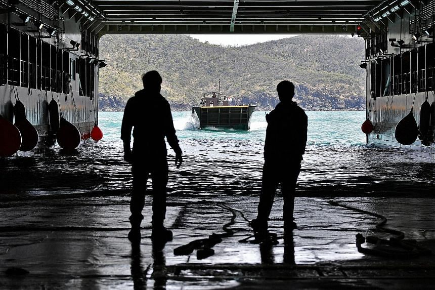 Sailors working in the well dock of the RSS Resolution as it prepares to receive a fast craft. The well dock allows the fast craft to sail into the ship where troops, equipment and vehicles can be dropped off.