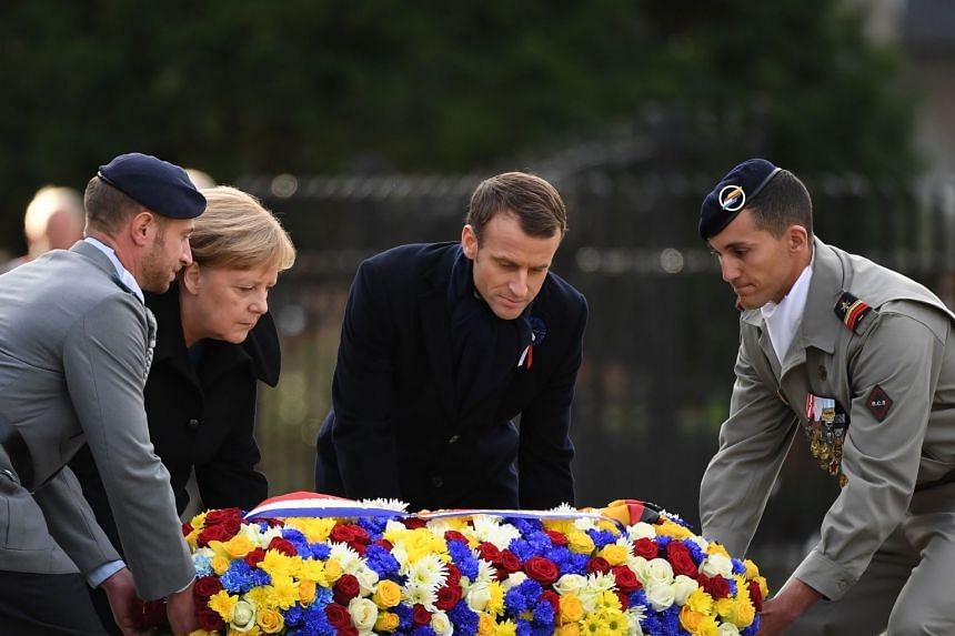 Merkel (second left) and Macron (second right) lay a floral wreath as part of the ceremony.