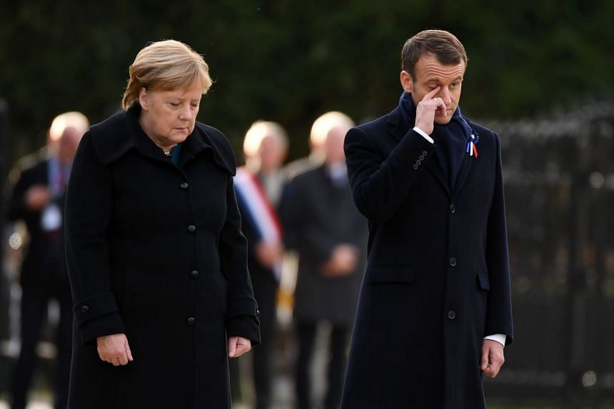 Merkel (left) and Macron stand as they take part in the French-German ceremony.