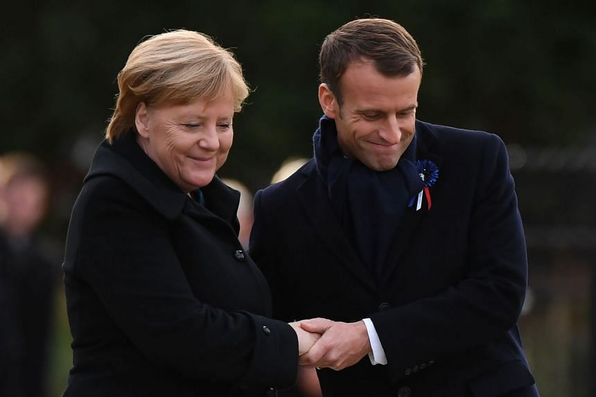 Merkel (left) and Macron embrace as they take part in the French-German ceremony.