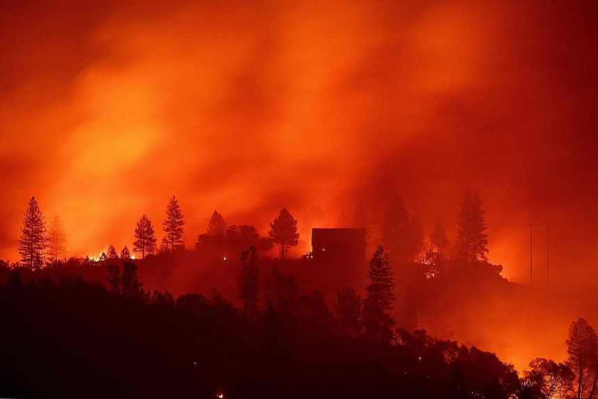 Flames from the so-called Camp Fire burning near a home atop a ridge near Big Bend, California, last Saturday. The fire has killed at least 23 people.