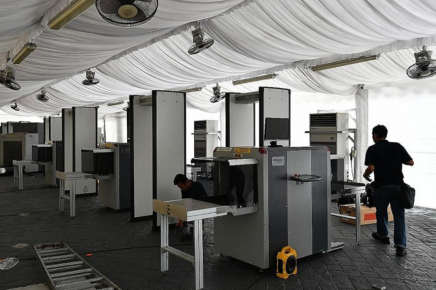 Security personnel setting up X-ray machines and walk-through metal detectors near Suntec Singapore International Convention and Exhibition Centre, the summit venue, yesterday. The area around the venue has been declared an enhanced-security special