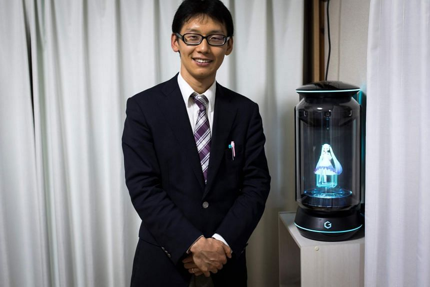 Mr Akihiko Kondo poses next to a hologram of Japanese virtual reality singer Hatsune Miku at his apartment in Tokyo, a week after marrying her.
