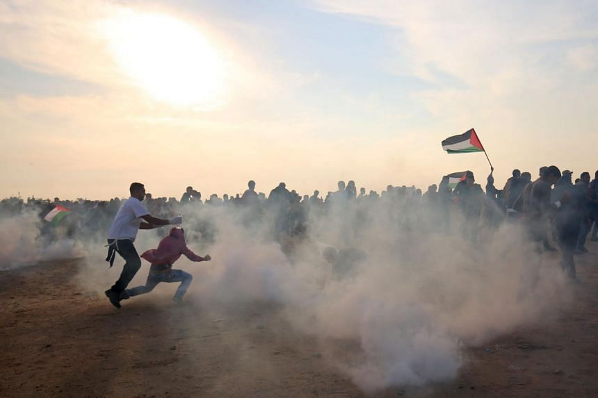 Palestinians run for cover from tear gas during clashes near the border between Israel and Khan Yunis in the southern Gaza Strip, on Nov 9, 2018.