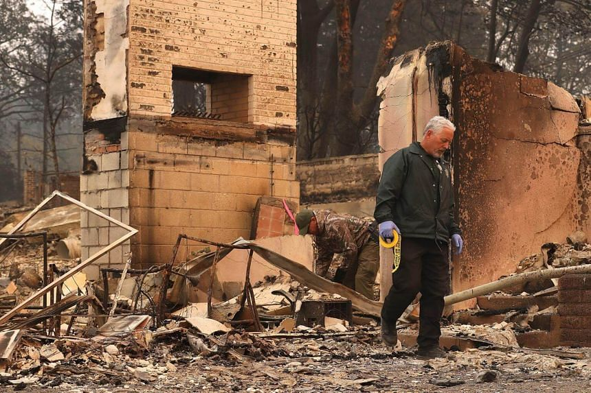 A Butte County sherriff deputy searches the property of a destroyed home for a reported Camp Fire victim, on Nov 10, 2018.