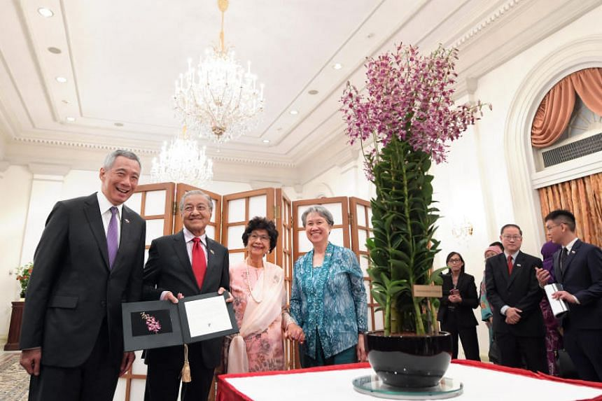 Malaysian Prime Minister Mahathir Mohamad and his wife Siti Hasmah Mohamad Ali at an orchid naming ceremony with Prime Minister Lee Hsien Loong and his wife Ho Ching at the Istana.