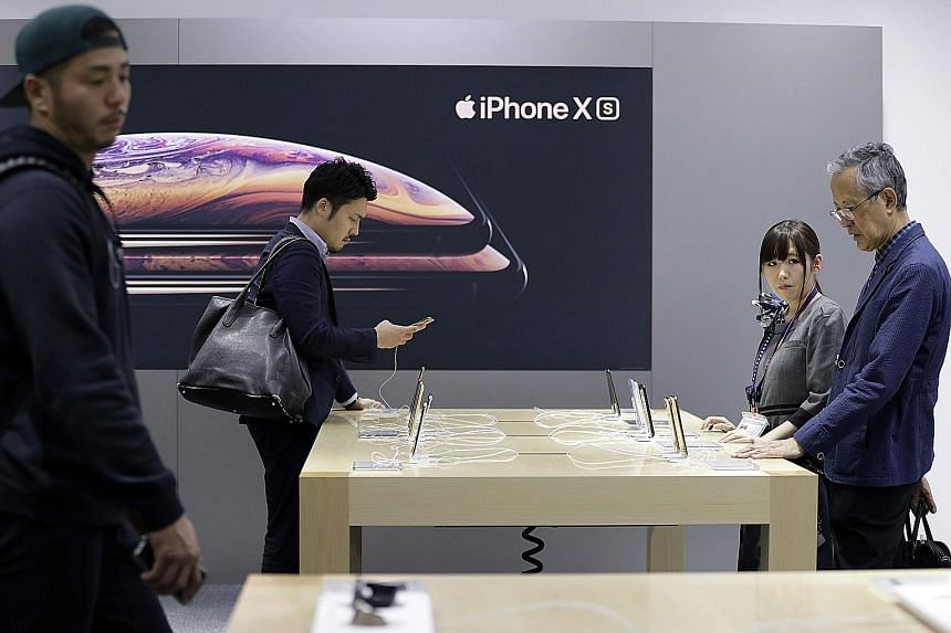 Customers trying out the Apple smartphones in a Tokyo store. The iPhone has become pricier with every new launch and analysts say that consumers, especially in emerging markets such as India, are ditching them for cheaper alternatives.