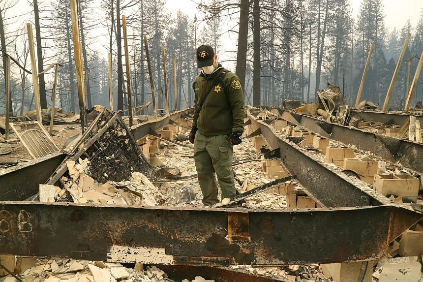 An investigator from the Fresno County Sheriff's Department searching the remains of a home at Ridgewood Mobile Home Park on Monday, in the aftermath of the Camp Fire blaze in Paradise, California.