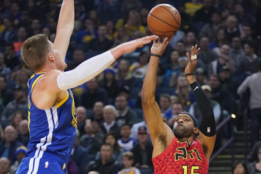 Atlanta Hawks forward Vince Carter (right) shoots the basketball against Golden State Warriors forward Jonas Jerebko during the first quarter at Oracle Arena.