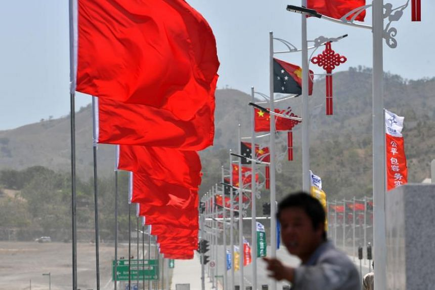 Workers make the final touches in preparation for Chinese President Xi Jinping's arrival and the welcoming ceremony, ahead of the Asia-Pacific Economic Cooperation summit in Port Moresby, Papua New Guinea.