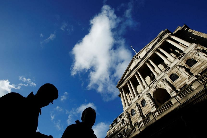 People pass the Bank of England in the City of London.