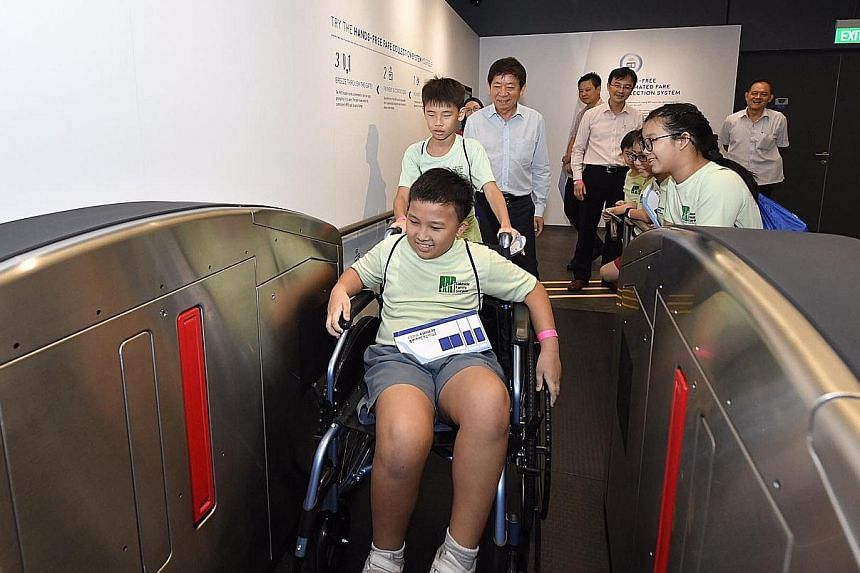Ten-year-old Parry Tan getting a first-hand experience of how wheelchair users can use hands-free MRT station fare gates yesterday. He was among some 30 visitors to the Singapore Mobility Gallery at the Land Transport Authority's headquarters in Hamp