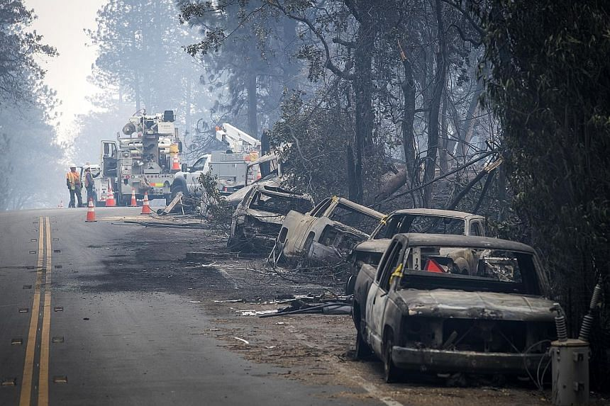 AT&T workers repair telephone lines on a road filled with burned-out vehicles in Paradise, California.