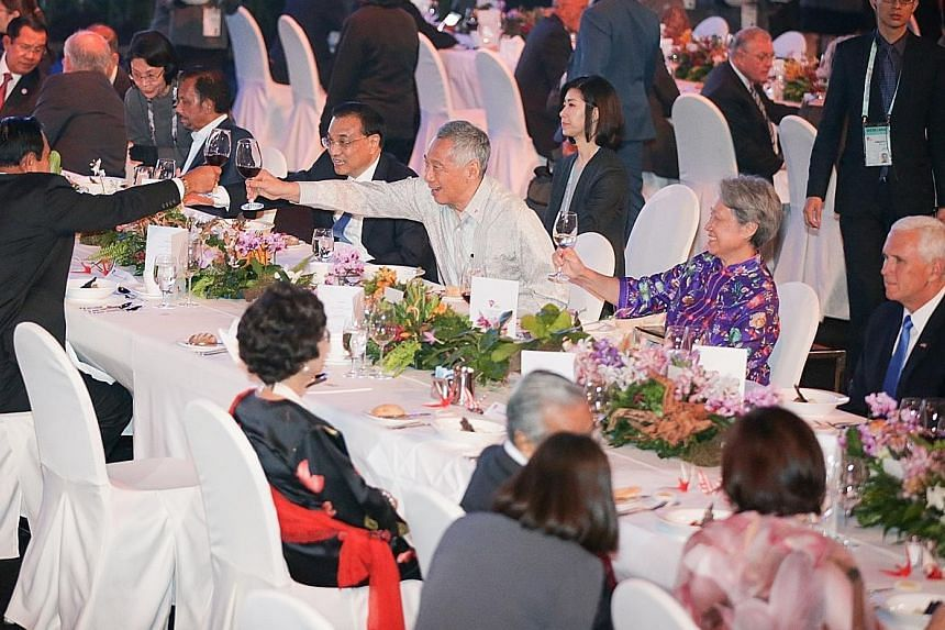 Prime Minister Lee Hsien Loong, Chinese Premier Li Keqiang and Thai Prime Minister Prayut Chan-o-cha (back facing camera) sharing a toast at last night's gala dinner. With them are Mrs Lee, American Vice-President Mike Pence (far right) and Brunei Su