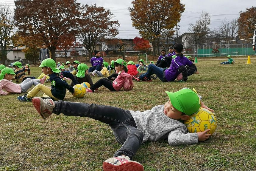 A Japanese boy stretching with a ball during a clinic arranged by J2 football club Matsumoto Yamaga with the Matsumoto City Kiri Kindergarten. Some 120 children from the kindergarten spent two hours with four Singaporeans and coaches from Yamaga, kic