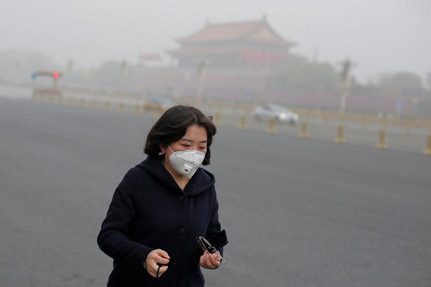 A woman wears a mask as Tiananmen Square is shrouded in haze after a yellow alert was issued for smog in Beijing, China, on Nov 14, 2018.