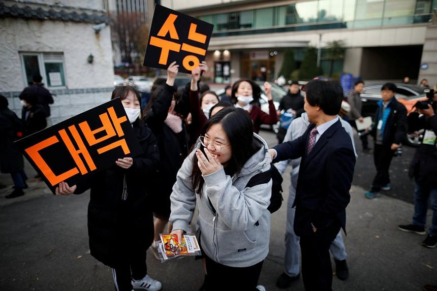 High school students cheer on a senior schoolmate (centre) before she takes the annual college entrance examinations, in Seoul, South Korea, on Nov 15, 2018.