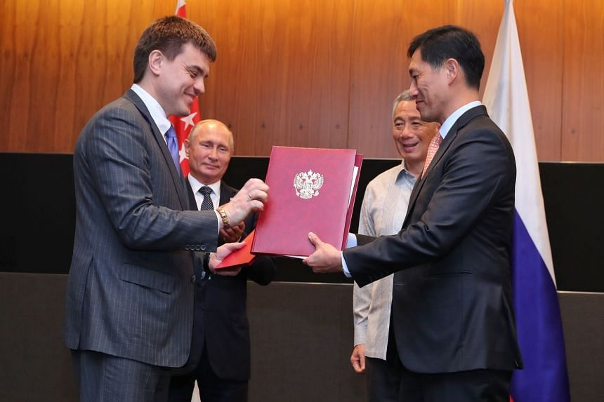 Ministers Mikhail Kotyukov and Ong Ye Kung exchange a Memorandum of Understanding between Russia's Ministry of Science and Higher Education and Singapore's Ministry of Education, watched by Prime Minister Lee Hsien Loong and Russian President Vladimi