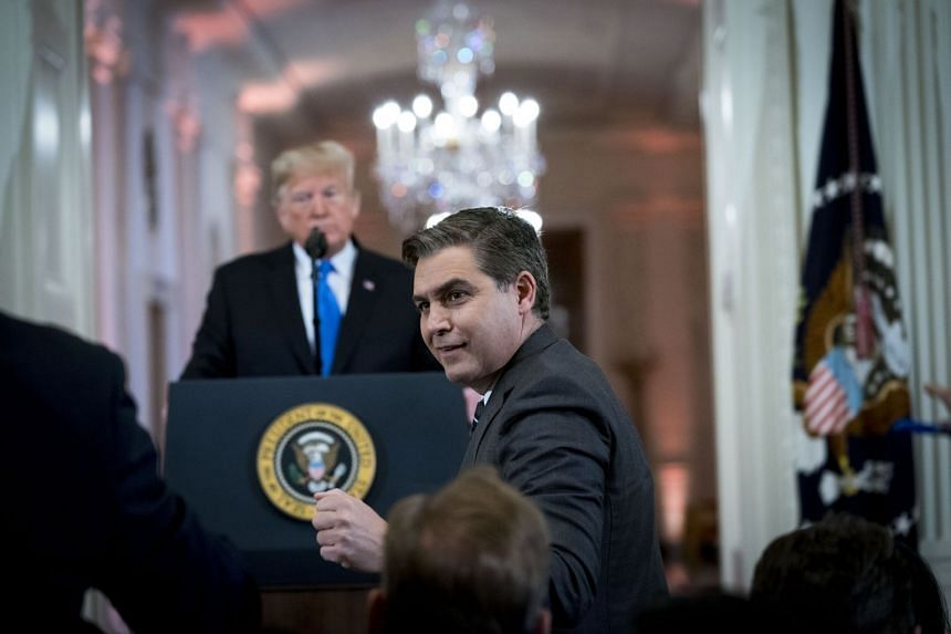 CNN reporter Jim Acosta waiting for the microphone at a news conference with President Donald Trump.