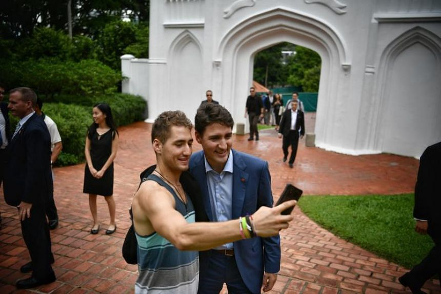 Canadian Prime Minister Justin Trudeau poses for a photo with a visitor at Fort Canning Park on Nov 15, 2018.