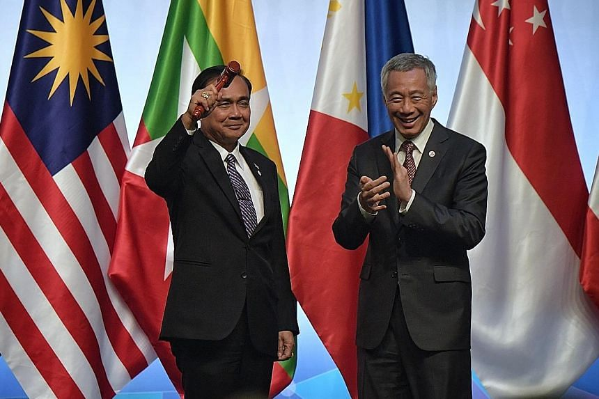 Thailand's Prime Minister Prayut Chan-o-cha holding the chairman's symbolic gavel after receiving it from Prime Minister Lee Hsien Loong at the closing ceremony of the 33rd Asean Summit yesterday. Thailand takes over the chairmanship of Asean from Si