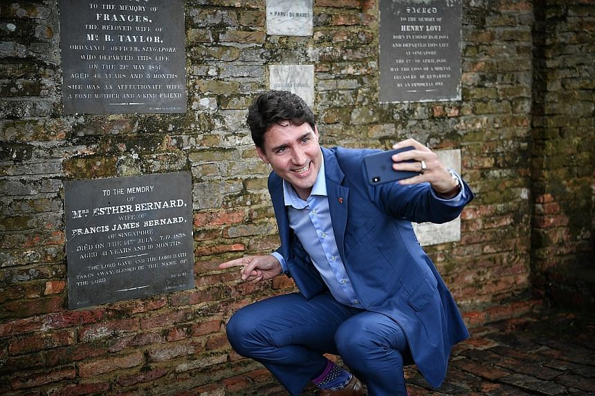 Canadian Prime Minister Justin Trudeau sending a video text of his maternal great-great-great-great-grandmother Esther Farquhar Bernard's memorial plaque to his son at Fort Canning Park yesterday.