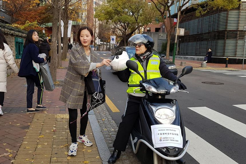 A student arriving at Ewha Girls' High School in Seoul for the national university entrance exam on Nov 15, 2018, escorted there by a motorbike that is one of hundreds of emergency vehicles dispatched on the roads to help ferry students running late.