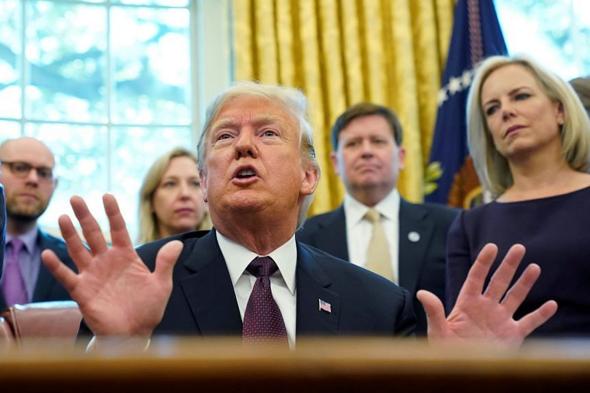 Trump talking to reporters at a White House signing ceremony for the Cybersecurity and Infrastructure Security Agency Act.