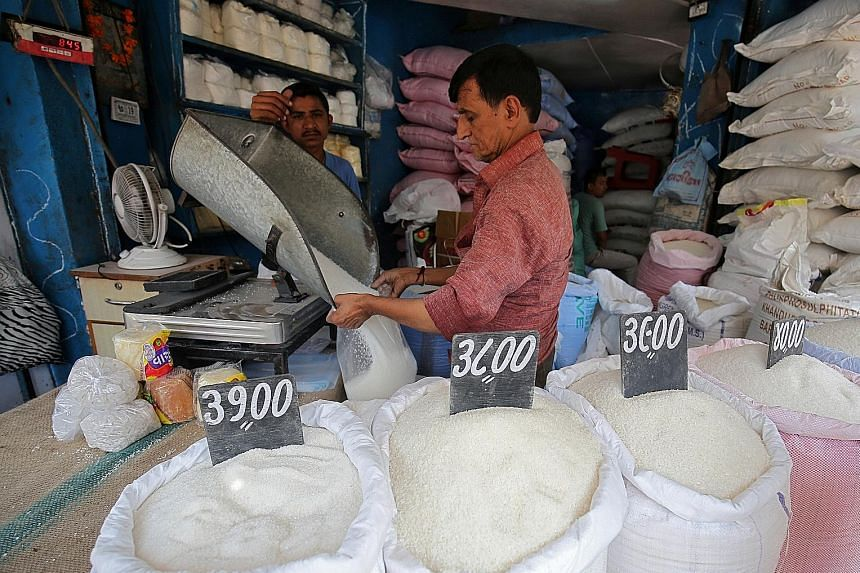 A worker packing sugar at a marketplace in Ahmedabad, India. Besides Australia, major sugar producers including Brazil and Thailand have also blamed India for contributing to a glut in the market that has forced prices down.