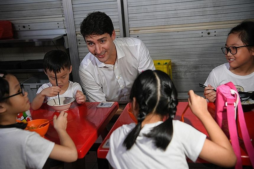 Canadian Prime Minister Justin Trudeau chatting with Ms Brenda Lim's children (from left) Rizuan, six, Long Jun, four, Zai Men, eight, and Yue Zuan, nine, during an early morning visit to Adam Road Food Centre yesterday.