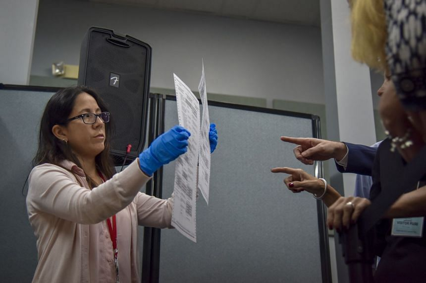 An election worker in Broward County shows to election observers ballots that have been damaged and duplicated in the recount for three statewide races.